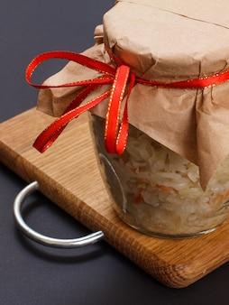 나무 커팅 보드와 검은색 배경에 유리 항아리에 당근을 넣은 홈메이드 발효 양배추. 비건 샐러드. 요리는 비타민 u가 풍부합니다. 건강에 좋은 음식입니다. 평면도.