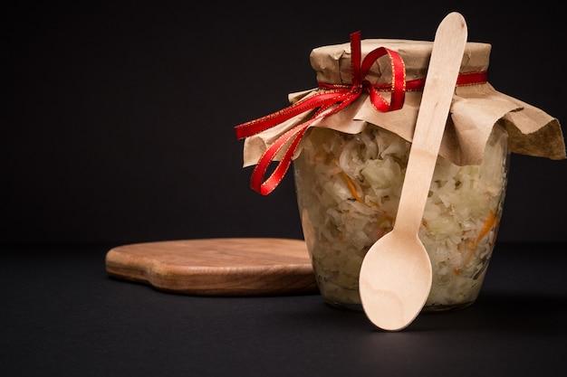 검은 배경에 나무 커팅 보드에 유리 항아리에 당근과 홈메이드 발효 양배추. 비건 샐러드. 요리는 비타민 u가 풍부합니다. 건강에 좋은 음식입니다.