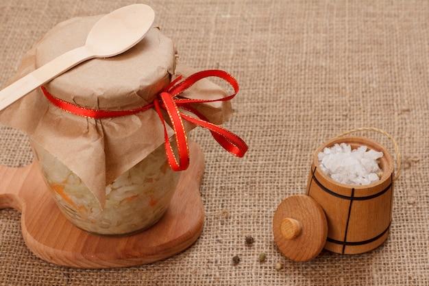 유리병에 당근을 넣은 홈메이드 발효 양배추, 작은 나무 통에 소금, 자루천 위에 숟가락. 비건 샐러드. 요리는 비타민 u가 풍부합니다. 건강에 좋은 음식입니다.