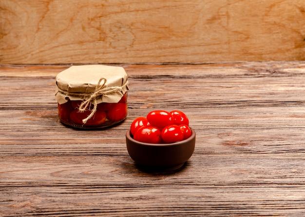 나무 배경에 갈색 그릇과 유리 항아리에 만든 발효 절인 토마토