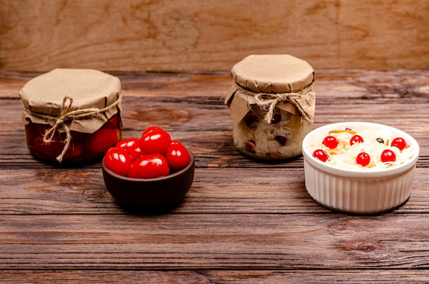 Homemade fermented pickled tomatoes and sauerkraut with cranberries in bowls on a wooden background.