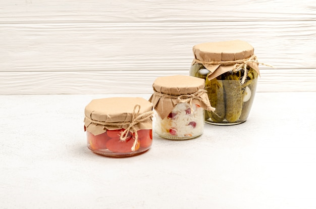Homemade fermented products in glass jars - sauerkraut, pickled tomatoes, pickles, light gray background.