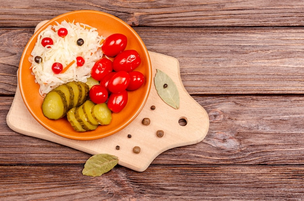 소금에 절인 양배추, 토마토, 나무 보드에 피클-접시에 만든 발효 제품