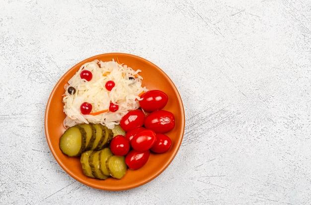 접시에 수제 발효 제품-소금에 절인 양배추, 토마토, 피클