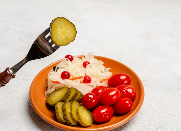 Homemade fermented products on a plate, sauerkraut, pickled tomatoes, pickles, light gray background. on a fork is a slice of pickled cucumber.