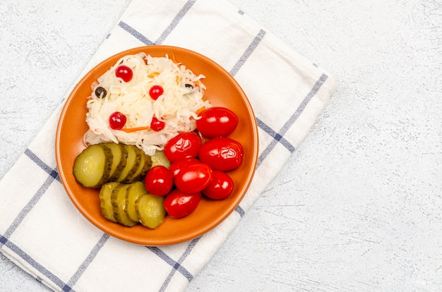 Homemade fermented products on a plate, sauerkraut, pickled tomatoes, pickles, light gray background.
