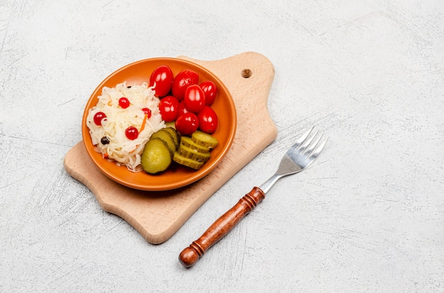 Homemade fermented products on a plate and wooden board, sauerkraut, pickled tomatoes, pickles, light gray background.