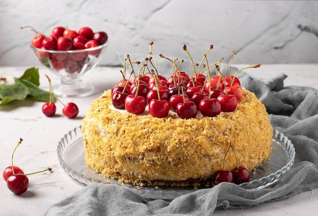 灰色の背景に甘いサクランボと自家製のお祝いケーキ。閉じる。ケーキの上部は新鮮な甘いサクランボで飾られています