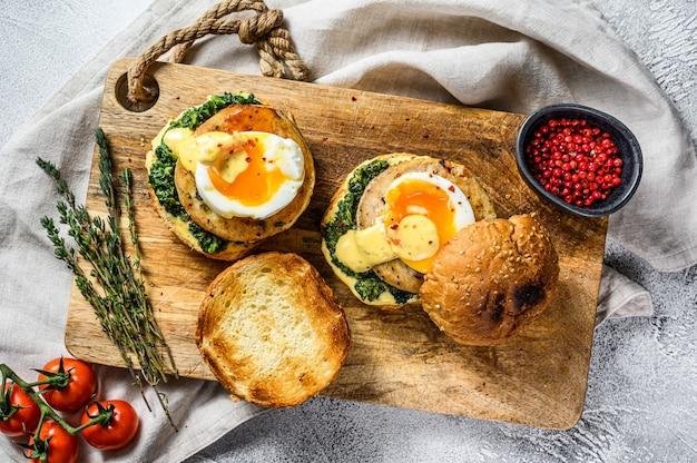 タラの切り身、卵、ほうれん草のブリオッシュパンの自家製魚バーガー。灰色の背景。上面図