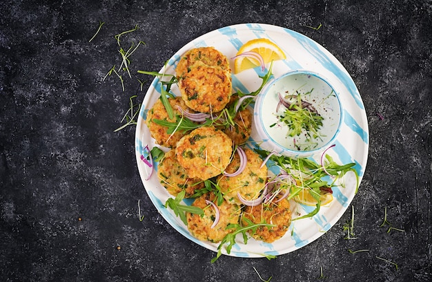 Домашний рыбный крокет с белой рыбой, булгуром, шпинатом и панировочными сухарями. оладьи из фарша трески. вкусный и питательный обед или ужин. вид сверху, сверху