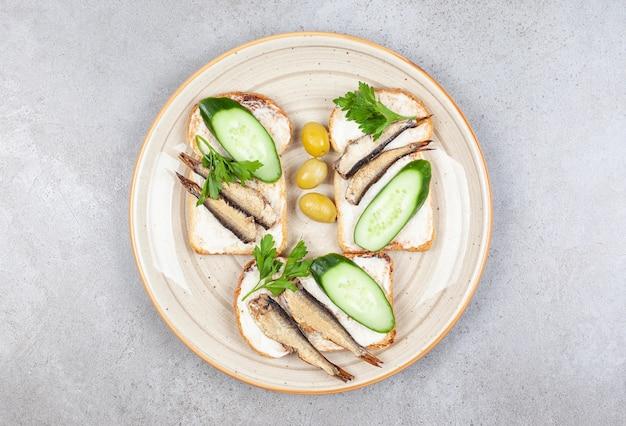 Самодельные бутерброды с рыбой на тарелке над серой поверхностью.