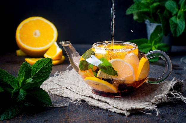 暗い素朴な背景のガラスのティーポットにオレンジとレモンのスライス、ベリー、ミント、蜂蜜を入れた自家製フレーバーフルーツティー。熱い秋または冬の飲み物。やかんにお湯が注がれています。