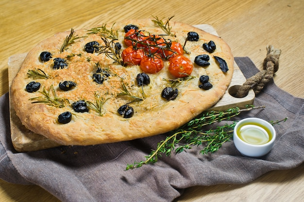 Homemade focaccia on a wooden table.