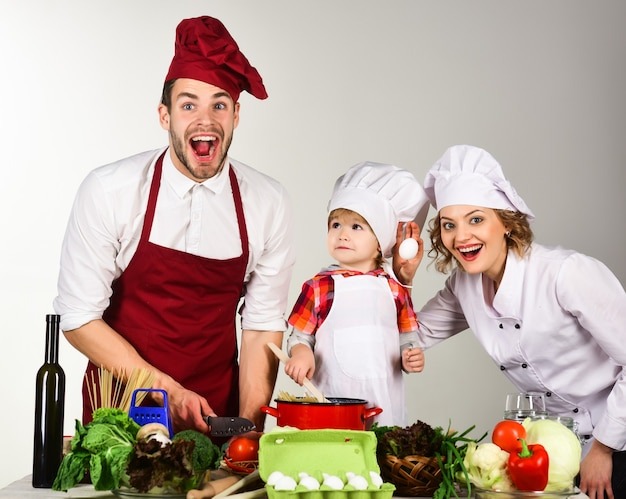 Homemade food happy family in kitchen healthy food at home adorable kid in chef hat preparation to