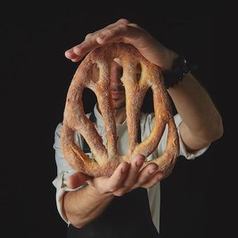 パン屋の手にある自家製フーガスパン