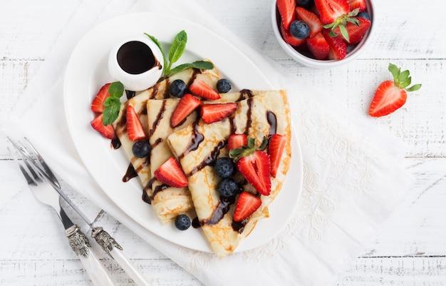 수제 프랑스 크레페 수 제트 팬케이크와 초콜릿 소스, 신선한 딸기, 꿀이 아침 식사로 화이트 세라믹 접시에 담겨 있습니다. 텍스트 또는 레시피를위한 공간입니다. 평면도.
