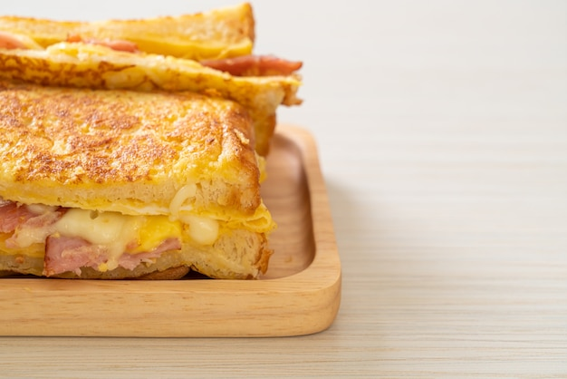 Домашний бутерброд с французскими тостами, ветчиной, беконом, сыром и яйцом