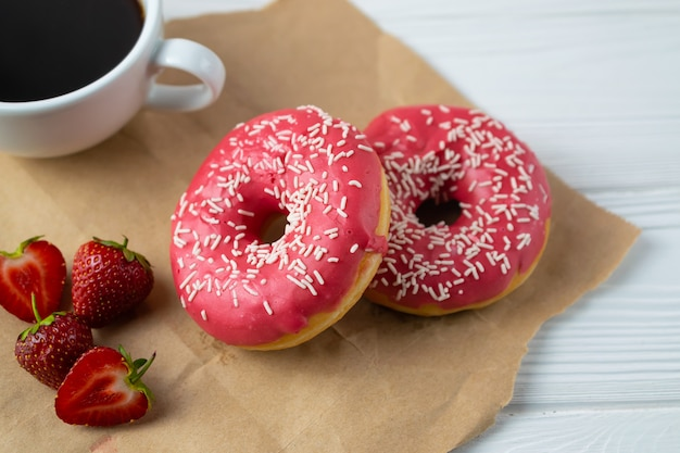 Homemade fresh baked donuts with strawberry pink frosting and black coffee