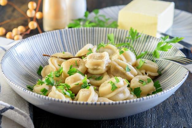 木製にスパイス、塩、バターを添えたモダンな青いボウルに自家製の焼きたての餃子