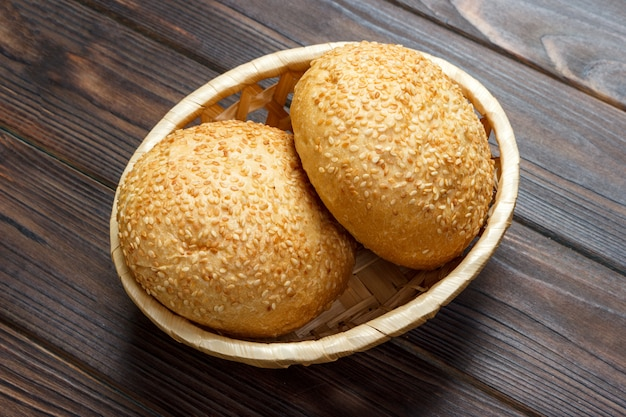 Homemade fresh buns in a basket on old wooden table