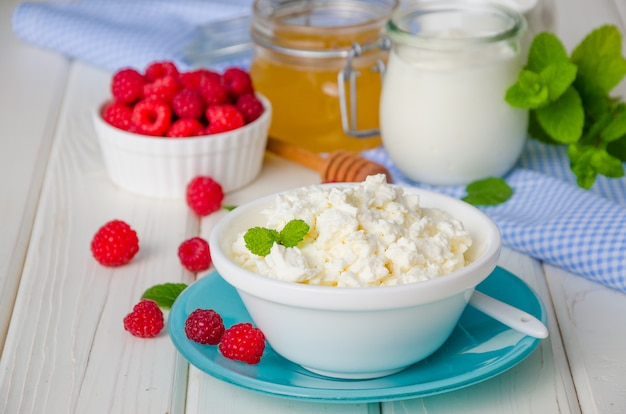 Homemade fresh cottage cheese in a bowl with berries of raspberry