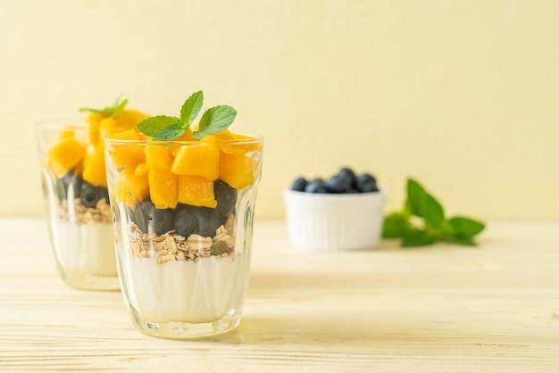 自家製の新鮮なマンゴーとヨーグルトとグラノーラを添えた新鮮なブルーベリー-健康的な食事スタイル