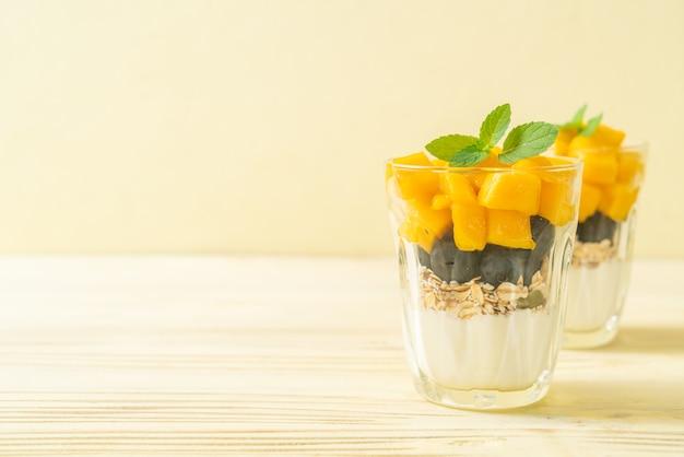 홈메이드 신선한 망고와 요구르트와 그라놀라를 곁들인 신선한 블루베리 - 건강식 스타일