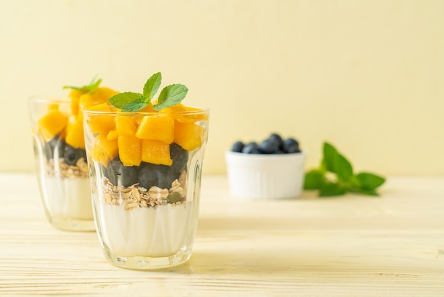 Homemade fresh mango and fresh blueberry with yogurt and granola - healthy food style