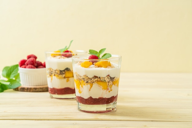 Homemade fresh mango and fresh raspberry with yogurt and granola - healthy food style