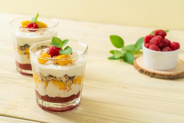 Homemade fresh mango and fresh raspberry with yogurt and granola. healthy food style