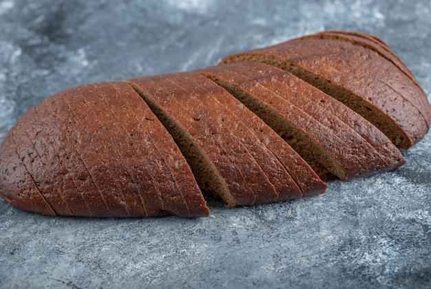 自家製の新鮮な有機パンパーニッケルライ麦パンをスライスにカット。高品質の写真