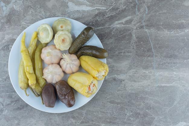 하얀 접시에 집에서 만든 신선한 절인 야채입니다.