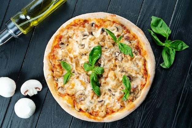 スモークチキン、マッシュルーム、バジル、ホワイトソースのコピースペース付きの黒い木製の自家製新鮮なピザ。