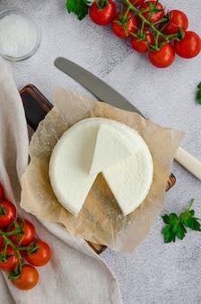 Домодельный свежий мягкий сыр или фета на деревянной разделочной доске с томатами петрушки и вишни на серой предпосылке. вертикальная ориентация, вид сверху