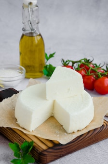 Домодельный свежий мягкий сыр или фета на деревянной разделочной доске с томатами петрушки и вишни на серой предпосылке.