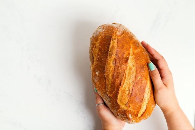 Homemade freshly baked natural healthy bread in a woman's hands on a light grey marble background.