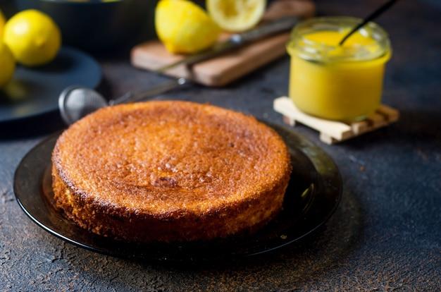 Homemade freshly baked sponge cake on plate, lemon kurd in a glass jar with spoon, whole and sliced fresh lemons on plate over dark background. copy space.