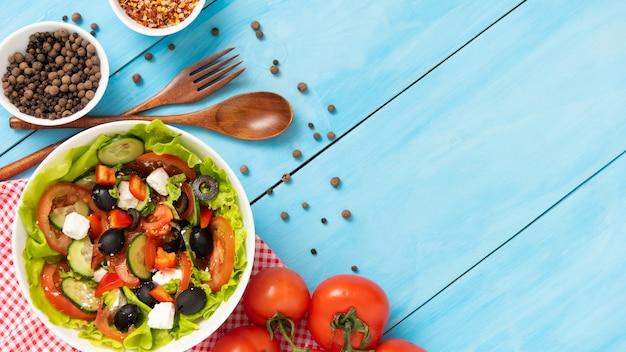 さまざまな調味料を使った青いテーブルの上に自家製の作りたてのギリシャ風サラダ。コピースペースのある上面図。