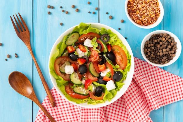 さまざまな調味料を使った青いテーブルの上に自家製の作りたてのギリシャ風サラダ。上面図。