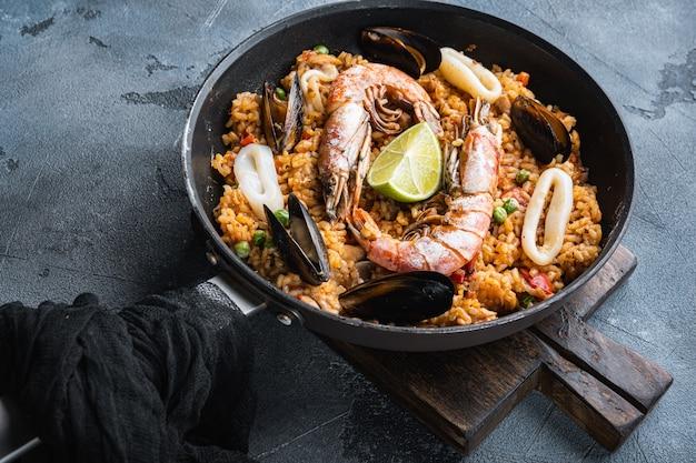 Домашняя свежеприготовленная паэлья с курицей и морепродуктами на сером текстурированном фоне, фото еды.