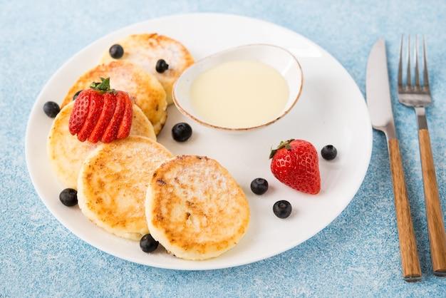 농축 우유와 딸기와 함께 만든 튀긴 치즈 케이크를 닫습니다.