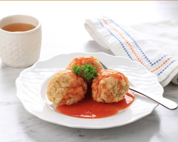 Домашний жареный цыпленок или фрикадельки с креветками (bakso goreng bandung), сервированный на белой тарелке с чашкой чая
