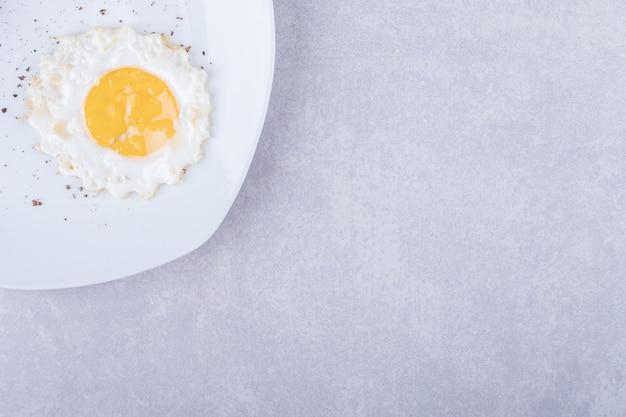 Uovo fritto casalingo sul piatto bianco.
