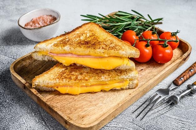 Домашний жареный бутерброд с ветчиной и сыром на разделочной доске