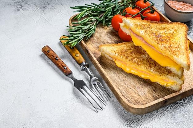 커팅 보드에 집에서 튀긴 햄과 치즈 샌드위치