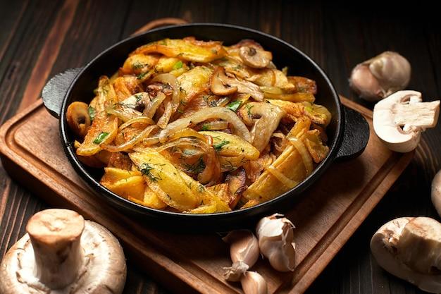 Домашний жареный картофель с луком, грибами и чесноком на сковороде, на деревянной доске