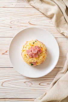 Домашний жареный рис с ветчиной на тарелке