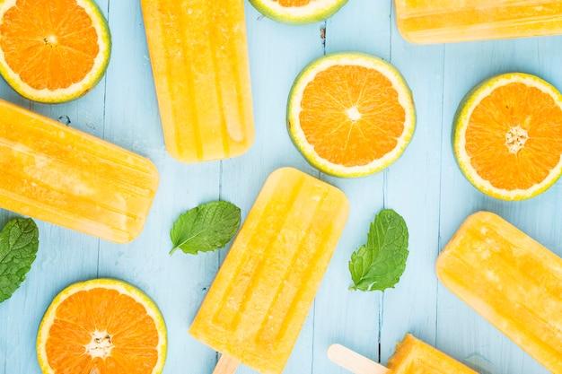 Домашнее морозное фруктовое мороженое с апельсинами на синем деревянном
