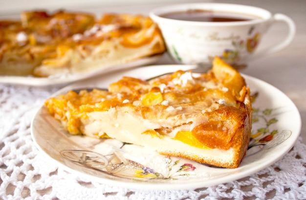 Домашний фруктовый яблочный абрикосовый персиковый пирог крупным планом на белой вязанной салфетке