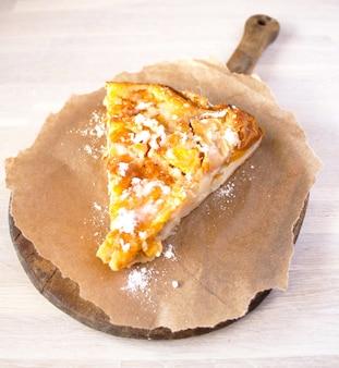 Домашний фруктовый яблочный абрикосовый персиковый пирог на крафт-бумаге на деревенской разделочной доске на белом столе